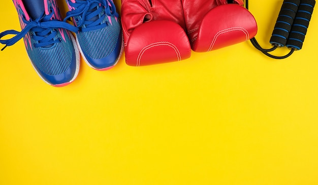 Paire de baskets bleues, gants de boxe en cuir rouge