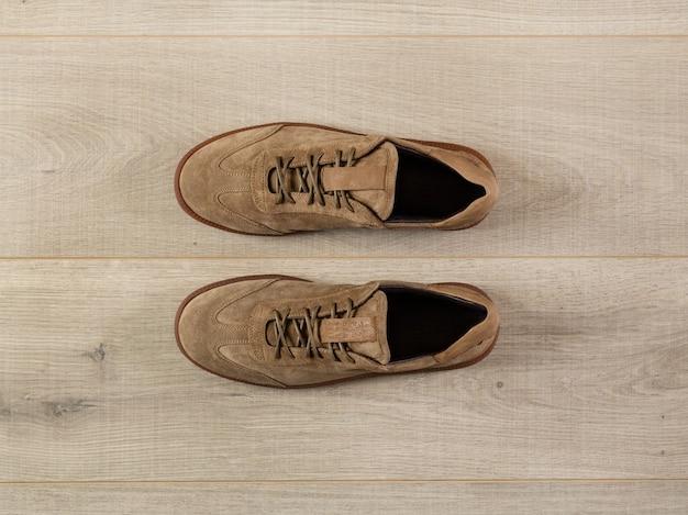 Une paire de baskets en daim souple sur fond de plan rapproché de surface de planche