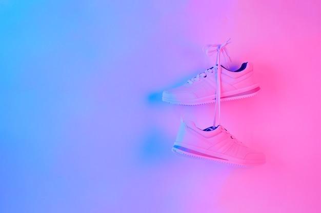 Paire de baskets élégantes accrochées au mur. chaussure blanche isolée sur fond néon. espace pour le texte.