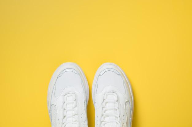 Paire de baskets femelles blanches sur fond jaune. lay plat, vue de dessus minimale.