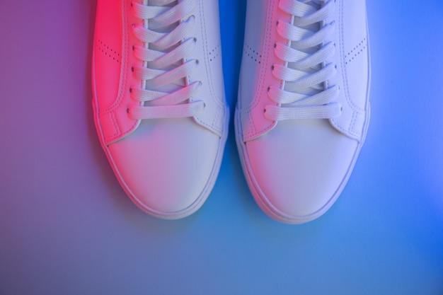 Paire de baskets sur fond de couleur, vue de dessus.