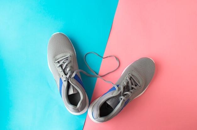 Paire de baskets neuves grises, sur fond bleu rose, lacets en forme de coeur