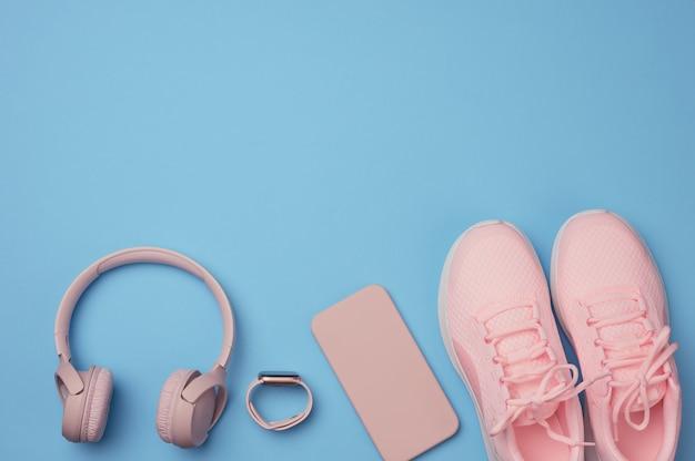 Paire de baskets roses, d'écouteurs sans fil, d'un smartphone et d'une montre intelligente sur une surface bleue. choses et gadgets pour le sport, la course à pied, la pose à plat