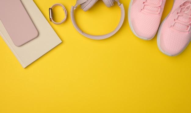 Paire de baskets roses, d'écouteurs sans fil, d'un smartphone et d'une montre intelligente sur une surface jaune. choses et gadgets pour le sport, la course à pied, place pour une inscription, mise à plat