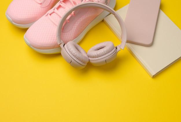 Paire de baskets roses, d'écouteurs sans fil, d'un smartphone et d'une montre intelligente sur une surface jaune. objets et gadgets pour le sport, la course à pied