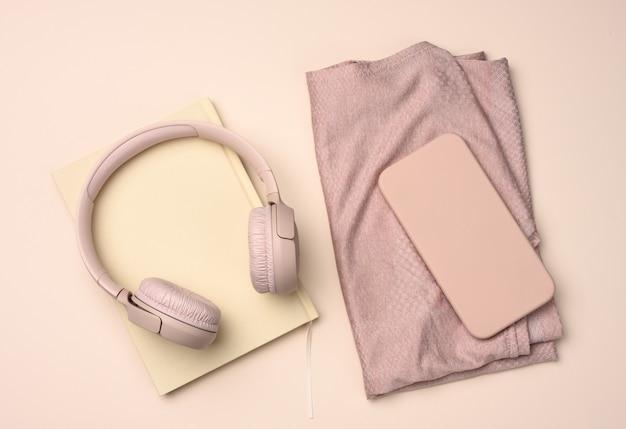 Paire de baskets roses, d'écouteurs sans fil, d'un smartphone et d'une montre intelligente sur une surface rose. choses et gadgets pour le sport, la course à pied, la pose à plat