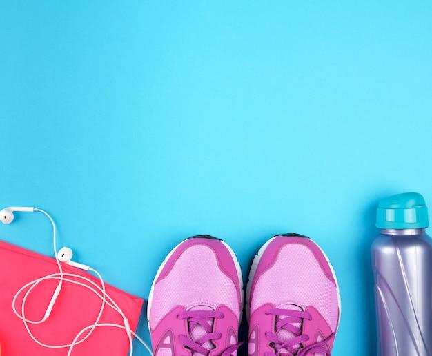 Paire de baskets roses à lacets sur fond bleu, vue de dessus, espace copie