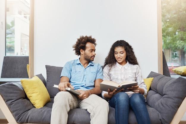 Paire de beaux jeunes étudiants à la peau noire assis dans la bibliothèque après les études, lisant des informations sur l'histoire ancienne, parlant, se préparant aux examens à l'université.