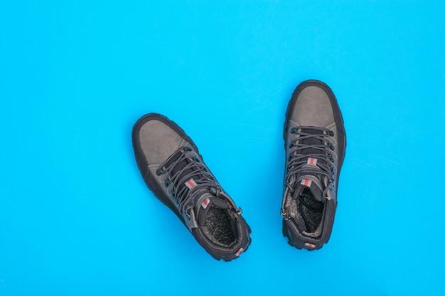 Une paire de bottes brutales pour hommes sur un bleu vif. chaussures homme pour temps froid. chaussures de sport décontractées pour hommes. mise à plat. vue d'en haut.