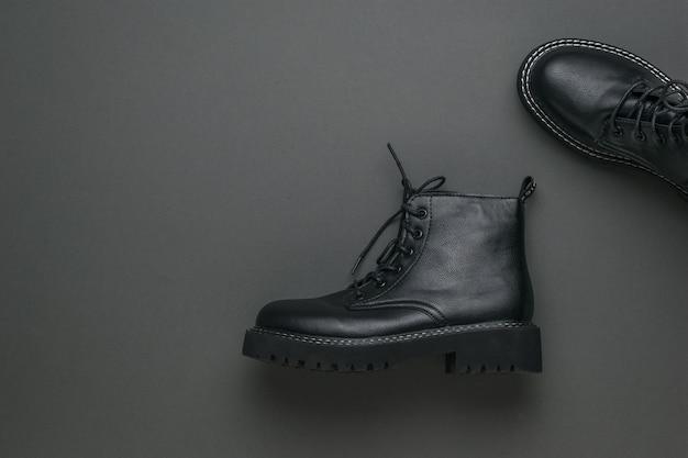Une paire de bottes en cuir noir élégantes sur une surface gris foncé