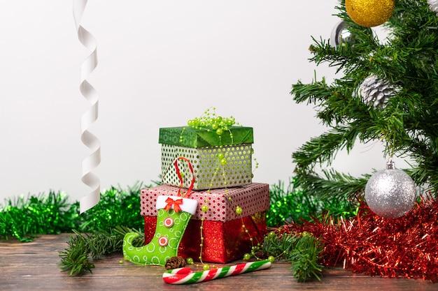 Une paire de cadeaux emballés dans un emballage de fête lumineux, sur lesquels sont des bas lumineux pour les bonbons
