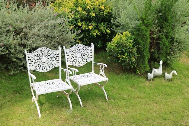 Paire de chaises en fer forgé blanc de style vintage dans un jardin verdoyant avec statues de famille du canard