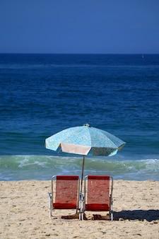 Une paire de chaises de plage rouges et un parasol bleu sur une plage de sable face à un océan bleu