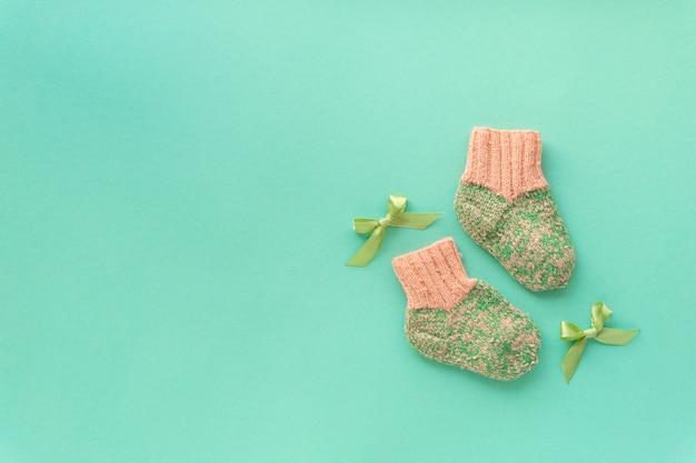 Paire de chaussettes bébé tricotées pour fille sur fond de menthe, copyspace.