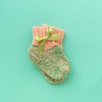Paire de chaussettes bébé tricotées pour fille sur fond de menthe, vue du dessus.