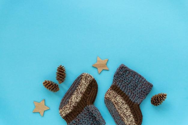 Paire de chaussettes bébé tricotées pour garçon sur fond bleu, copyspace.