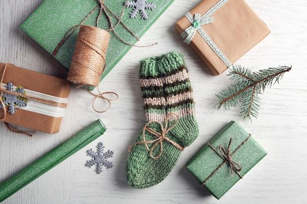 Paire de chaussettes tricotées avec des cadeaux emballés pour noël sur table lumineuse