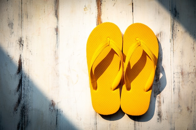 Paire de chaussons jaunes sur fond de bois.