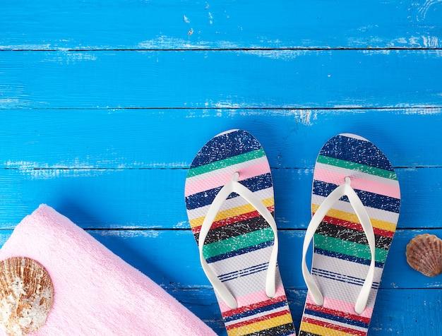 Paire de chaussons de plage et d'une serviette rose sur bleu