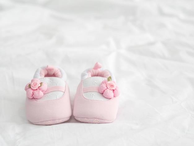 Une paire de chaussures de bébé rose sur la couverture avec espace copie