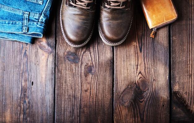 Paire de chaussures en cuir marron, portefeuille et jean