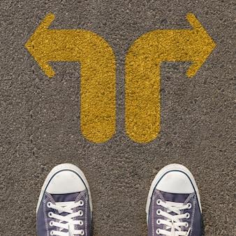 Paire de chaussures debout sur une route avec une flèche jaune à double sens