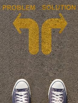 Paire de chaussures debout sur une route avec flèche