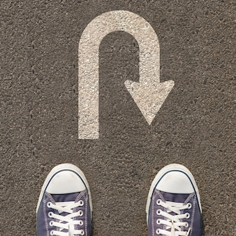 Paire de chaussures debout sur une route avec panneau de signalisation