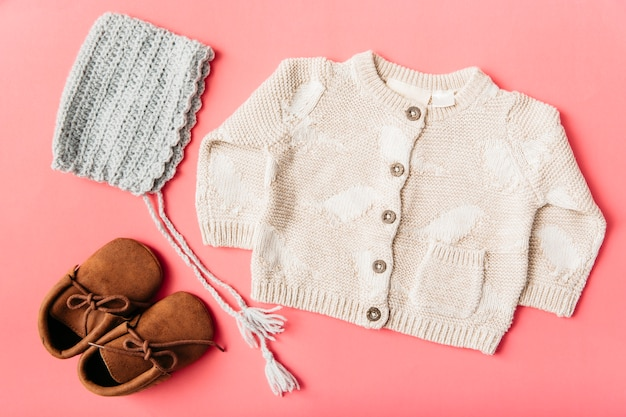 Paire de chaussures en laine; casquette et vêtements de bébé sur fond de pêche