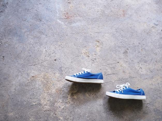 Paire de chaussures de sport bleues sur fond de béton grunge.
