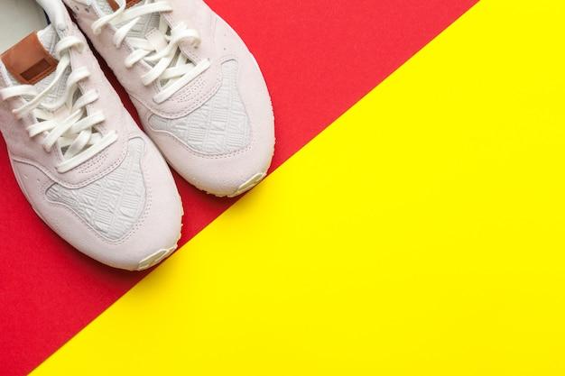 Paire de chaussures de sport sur fond coloré