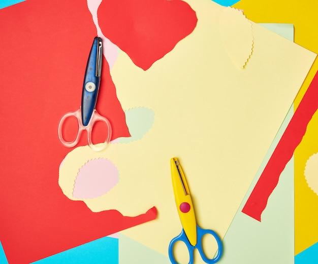 Paire de ciseaux en plastique et papier de couleur pour découper les figures