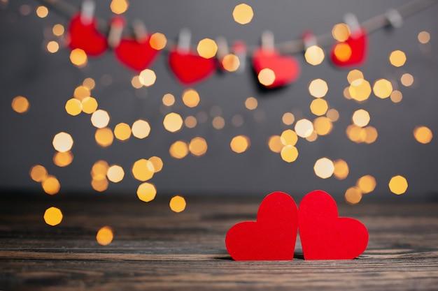 Paire de coeurs rouges sur fond de lumières, l'amour et la saint-valentin concept sur une table en bois