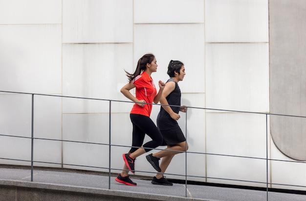 Paire de course à pied faisant de l'exercice à l'extérieur de la ville dans une photo de sport actif vivant en milieu urbain, avec des bâtiments en arrière-plan