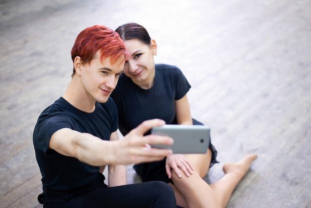 Paire de danseurs prenant le selfie sur le téléphone portable après la formation