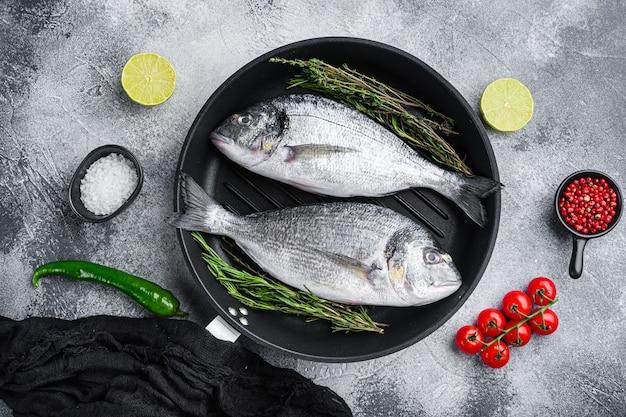 Paire de daurade ou dorado poisson cru sur lèchefrite avec des ingrédients sur gris