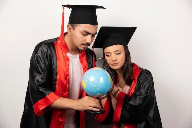 Paire d'étudiants en robe regardant globe avec loupe.