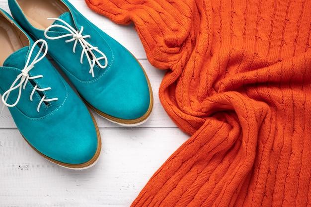 Paire de femmes oxford aqua et pull orange sur fond en bois blanc. concept de style branché plat, décontracté. vêtements à la mode.