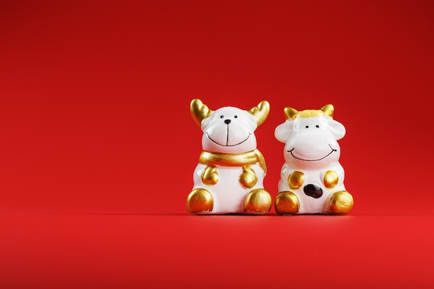 Une paire de figures de vache et de taureau sur fond rouge, avec espace libre