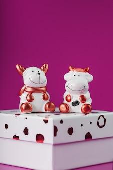 Une paire de figurines vache et taureau sur un coffret cadeau sur fond rose