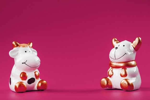 Une paire de figurines vache et taureau sur fond rose, avec espace libre