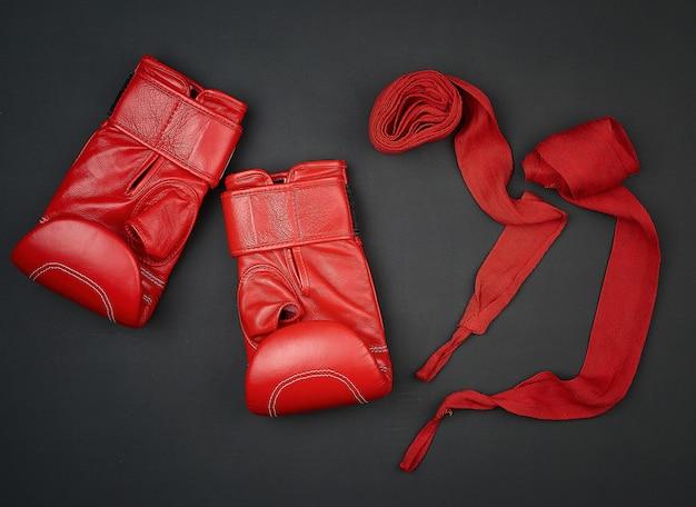 Paire de gants de boxe en cuir rouge et bandage textile rouge sur fond noir