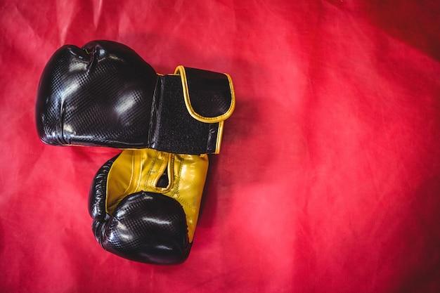 Paire de gants de boxe sur surface rouge