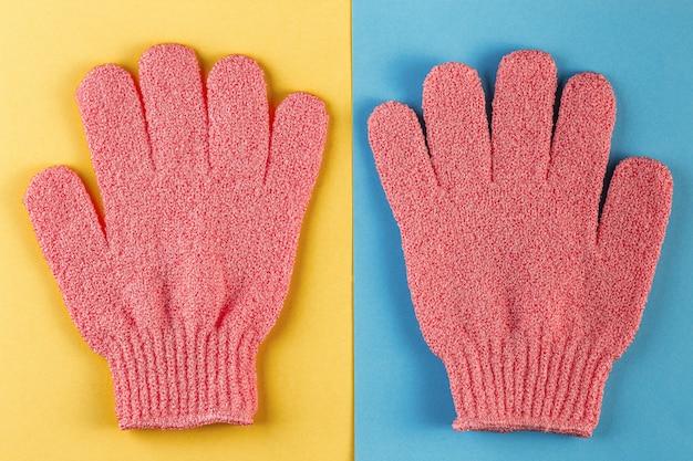 Une paire de gants de massage roses pour la douche sur fond bleu et jaune
