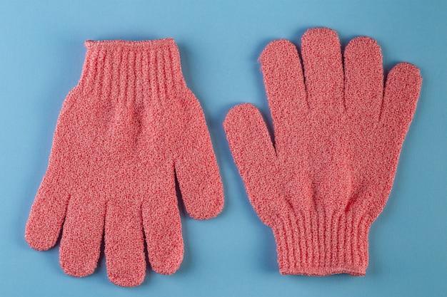 Une paire de gants de massage roses pour la douche sur fond bleu