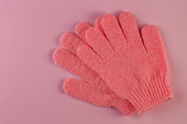 Une paire de gants de massage roses pour la douche sur fond rose