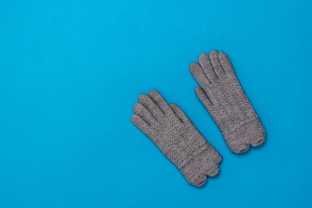 Une paire de gants tricotés gris pour femme sur fond bleu. accessoires pour femmes par temps froid.