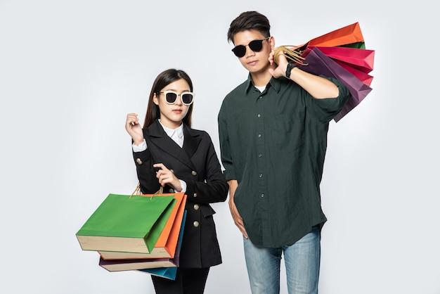 Une paire d'homme et de femme portant des lunettes et transportait beaucoup de sacs en papier pour faire du shopping