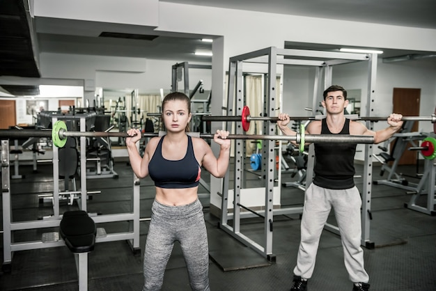Paire d'instructeur de formation avec une femme, les deux tenant des haltères