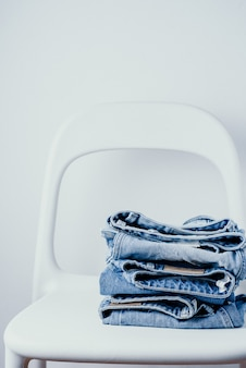 Paire de jeans sur une chaise blanche sur fond blanc